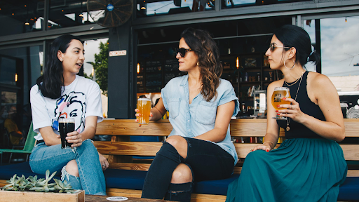 Three women holding beers, sitting on a bench, and having a conversation.
