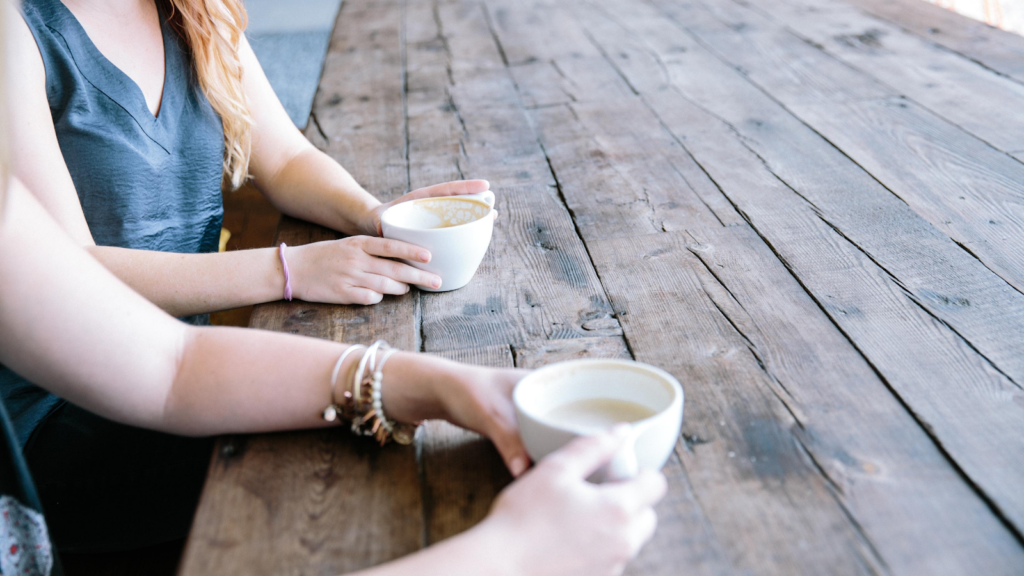 Two people holding cups of coffee at a large wooden table. Their faces are not visible.