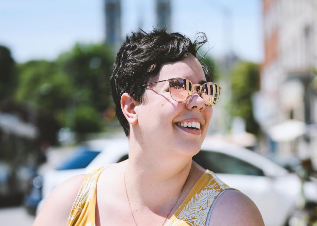 Portrait of author, Katrina Bell, smiling with sunglasses on.
